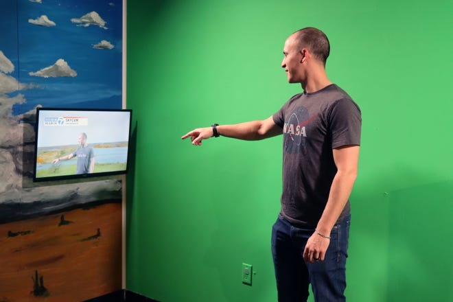 """Kyle Hadley, director of exhibits, demonstrates the green screen that is a part of the Don Harrington Discovery Center's news set, which is part of the upcoming exhibit call """"Geared Up: Futures in STEM"""" to be opened later this spring."""