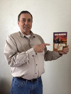 """Richie Brotherton holds a copy of his book, """"Just Beyond the Law."""""""