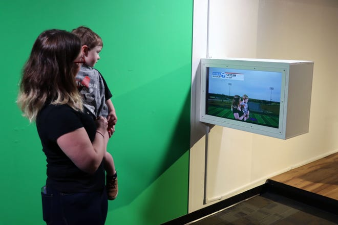 """Chantell and Soren Anderson stand in front of the green screen that is a part of the Don Harrington Discovery Center's news set, which is part of the upcoming exhibit call """"Geared Up: Futures in STEM"""" to be opened later this spring."""
