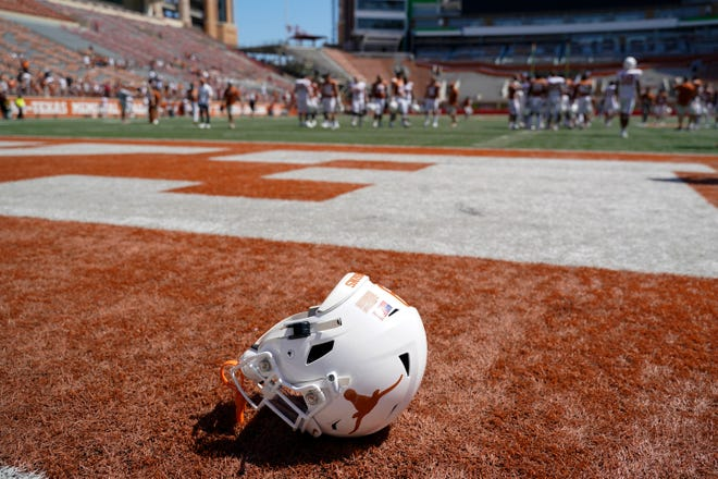 A Texas football helmet lays on the field after the Orange-White spring game on April 24. On Thursday, former UT associate athletics director Larry Falk, a fixture around UT sporting events for the better part of three decades, died.
