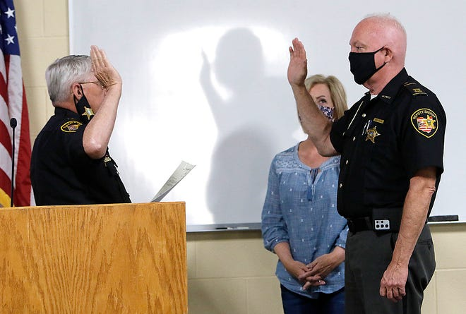 Sheriff E. Wayne Risner swears in Capt. Dave Blake as chief deputy as his wife, Elaine, stands next to him on Tuesday.