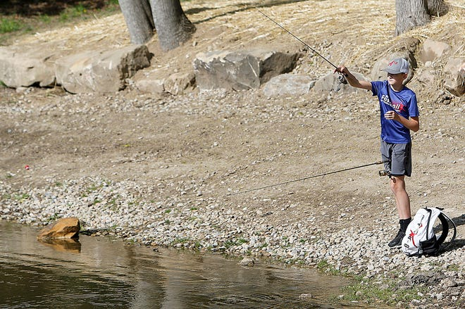 Kohler Scott fishes with two poles at the pond at Brookside Park in Ashland on Tuesday morning, taking advantage of the warm, sunny spring weather, which was expected to reach a high temperature of 80 degrees.