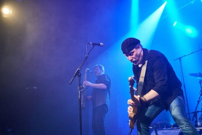 Bill Toms suona un po 'di chitarra, con il sassofonista Phil Brontz all'ombra.  Toms celebra l'uscita del suo decimo album in studio con uno spettacolo all'aperto a Chiswick.