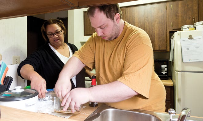 Marcey Henderson of Homewatch Caregivers helps client Daniel Blake. The company won a special award for meaningfulness in Columbus CEO's Top Workplaces 2021.