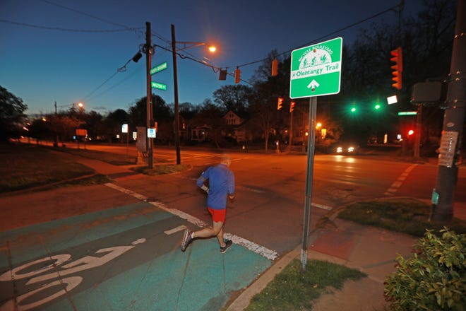 A runner on Milton Avenue crosses W. North Broadway Monday night. Columbus parks officials have selected a route to connect the Olentangy Trail through Clintonville.