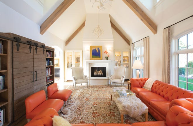 A cozy fireplace lights up the far side of the living room, and orange benches add additional seating.