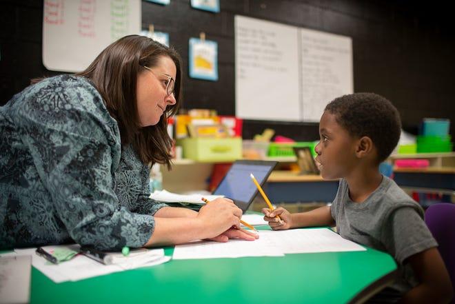 McDowell Elementary School kindergarten teacher Jerilyn Crooks assists  L.J. Gatlin on a composition project at the Columbia, Tenn., school on Tuesday, April 27, 2021.