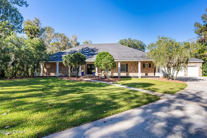 This beautiful home, nestled on 1.68 acres in New Smyrna Beach's gated community of Lake Waterford Estates, has an open-floor plan, a large double-entry circular drive, Chicago brick exterior, vaulted ceilings, formal living and dining rooms.