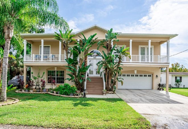This one-of-a-kind canal-front home in Astor offers views of the St. Johns River, along with a waterfront oasis, featuring an in-ground heated swimming pool, tiki hut, fire pit, a large boat lift, a small boat house (with smaller lift) and floating commercial dock.