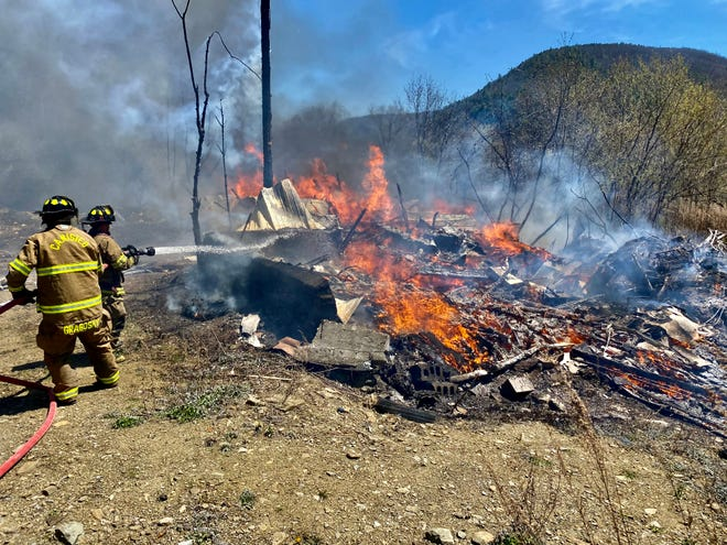Canisteo firefighters work to extinguish a structure fire on County Road 119 Monday.