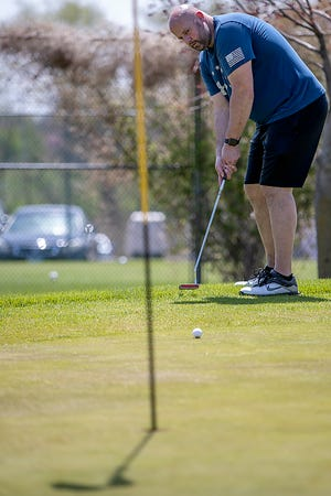 Galesburg resident Spencer Cochrane watches his putt from the fringe on the 9th green at Bunker Links on Tuesday, April 27, 2021.