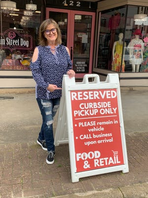 Ronelle Ianace poses next a sign highlighting curbside pickup. Ianace is one of two Denison business owners who have recently been recognized for business best practices during the pandemic.
