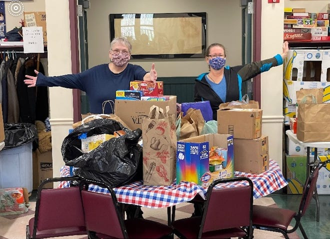 First Congregational Church volunteers Linda Polissack and Heather Beauregard with donations for the Millbury Senior Center's food pantry.