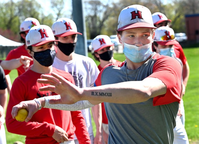 Dan Quinn, a captain on the Holliston baseball team, performs a throwing drill during the second day of practice Adams Field, April 27, 2021.
