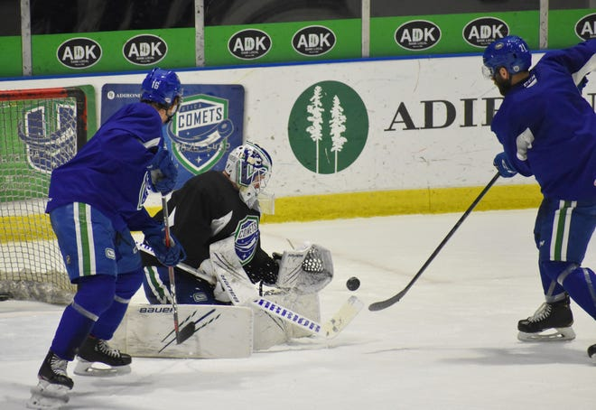 John Stevens (16) and Jonah Gadjovich (21) scramble for a rebound against Jake Kielly during Tuesday's Utica Comets practice. The team is scheduled to play 11 regular-season over the next 19 days.