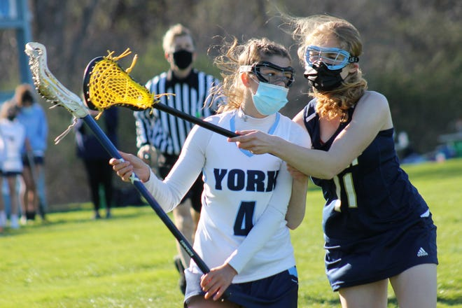 York's Clara Pavuk, left, is being covered tightly by Traip Academy's Isabella Harris during girls lacrosse action Monday in York, Maine.