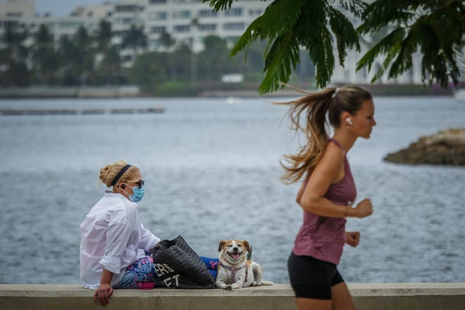 A runner passes by a woman with her dog at the seawall and nearby Meyer Amphitheater in downtown West Palm Beach, Fla., on Friday, April 17, 2020. Florida life continues under a stay-at-home order that will last into May. New cases of COVID-19 continue to be reported in Palm Beach County according to the Florida Department of Health, Division of Disease Control and Health Protection data. [THOMAS CORDY/palmbeachpost.com]