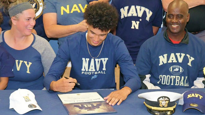 Forest Hill athlete Donovan Draper smiles as he pens his name, signing with the Naval Academy. Friends and family surrounded him on his celebratory signing at Forest Hill High on Tuesday morning.