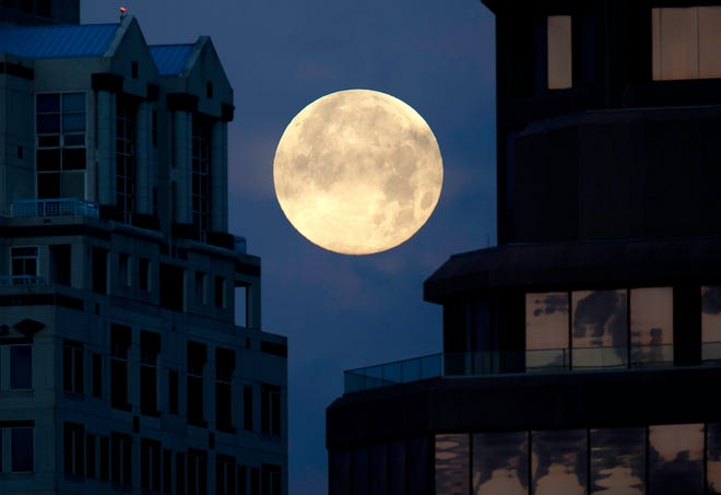 The full moon sets between the Esperante and Phillips Point buildings in West Palm Beach on Tuesday morning, April 27, 2021.