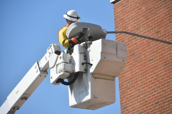 A Dominion Energy field technician fixes a new LED light onto a lamp post near the intersection of Tabb Street and Monroe Street in Petersburg.