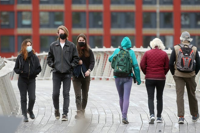 Masked walkers cross the Providence River Pedestrian Bridge on Tuesday.