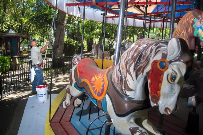 Presley Yen with the city of Stockton maintenance department paints the trim of the carousel at Pixie Woods children's playland in Louis Park in Stockton on April 27. Yen was a part of a crew sprucing up Pixie Woods in preparation for its June opening.