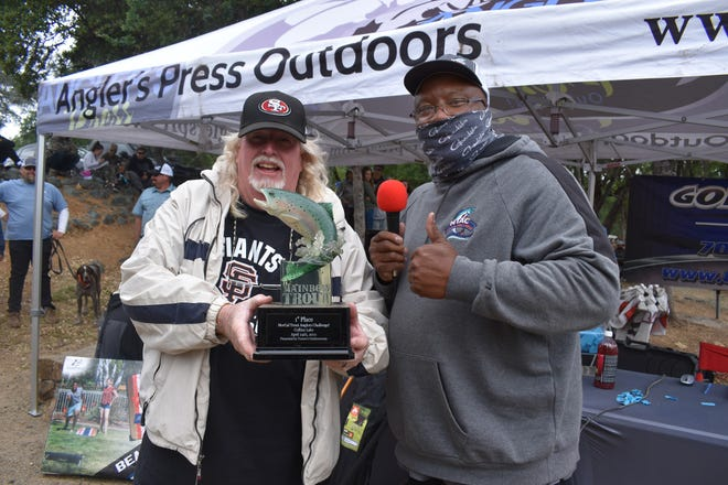 Mike Miller, with Sheldon Bright, holds up the custom trophy he was awarded for winningtheNTAC event at Collins Lakeon April 24 when he caught a 6.40-pound rainbow.
