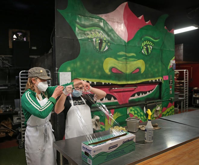 """Co-founder Catherine Pickup, left, shows employee Cole Peterman how to wrap food for storage in front of the """"Fire Breathing Oven"""" at Reality Kitchen in Eugene."""