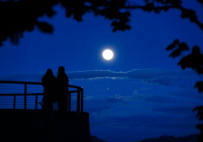 People gather on the overlook at Skinner Butte in Eugene to watch the Super Pink Moon rise over the Willamette Valley Monday night.