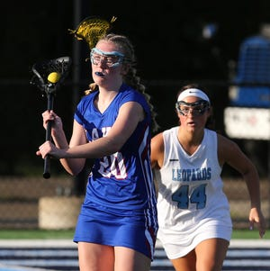 Emma Labbe (20) of Lake looks to pass while being trailed by Grace Reiman (44) of Louisville during their game at Louisville on Monday, April 26, 2021.