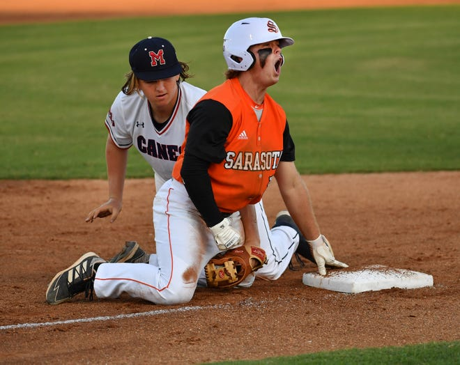 Sarasota High baserunner Bradley Ramsden reacts after sliding into third ahead of the tag by Manatee High third baseman Justin Cook in the third inning of their game Monday night at Sarasota High.