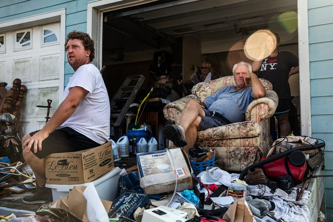 """Alex Garrish, left, and Dan Garrish sit with belongings from their flood damaged home, on Ocracoke Island, North Carolina, in September of 2019. While Hurricane Dorian largely spared the United States coast, it leveled a direct hit to Ocracoke Island, on the Outer Banks of North Carolina. """"I've been through every storm,"""" said Dan Garrish, 66. """"I've never seen water come in like this."""""""