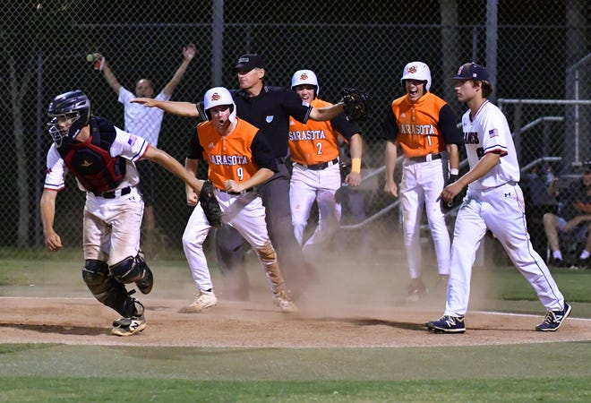 Sarasota High baserunners Garrett Browning #9, Carson Long #2 and Conner Whittaker #1, celebrate after they all scored on a single by Bradley Ramsden, to take the lead over Manatee High with two outs in the sixth inning.  The sailors won the game 6 to 4.