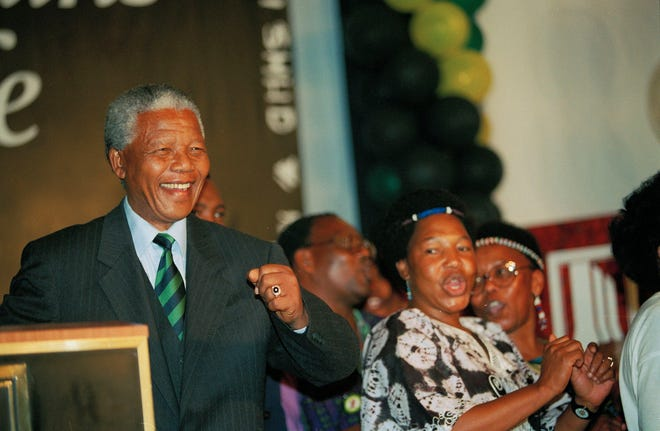 African National Congress President Nelson Mandela dances with supporters on his arrival to deliver his victory speech in downtown Johannesburg on May 2, 1994. Mandela became the first black president in South Africa's history.