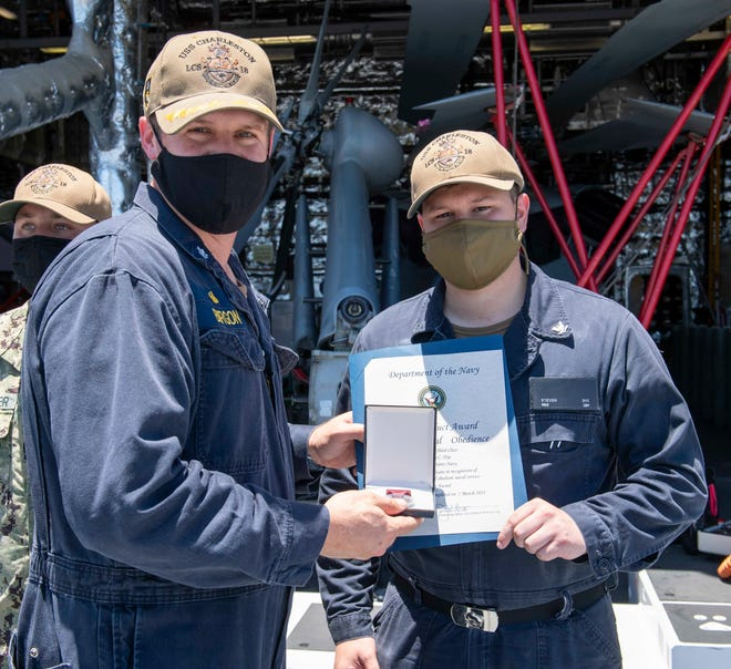 Mineman 3rd Class Steven Dye, right, from McLoud, receives the Navy Good Conduct Award from Cmdr. Joseph Burgon, left, from Cottonwood, California, aboard Independence-variant littoral combat ship USS Charleston (LCS 18), April 24. Charleston is currently operating in U.S. 3rd Fleet.