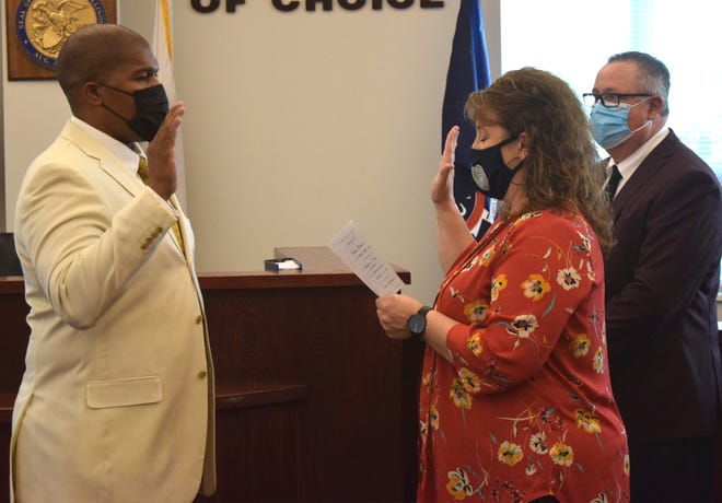 Tyrone Baker takes the oath of office as a councilman from City Clerk Rabecka Jones prior to Monday's City Council meeting. Mayor Gary Moore looks on at right.