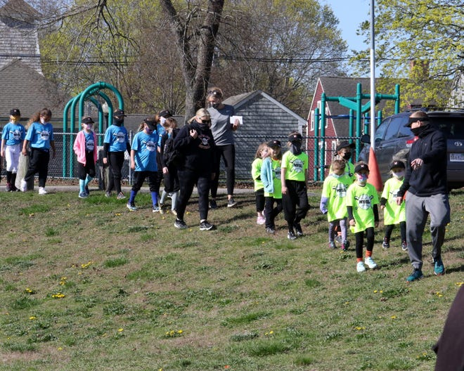 Players from the Peaceful Meadows and the Erica's Dance Academy teams lead the Middleboro Youth Softball League opening day parade Saturday at the Peirce Playground in Middleboro.