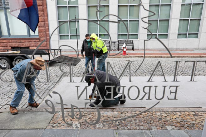 New Bedford DPI crew installs the outdoor seating area in front of Tia Maria's European Cafe as seen through the window of the downtown New Bedford restaurant.  These platforms were installed last year to help restaurants deal with COVID-19 seating restrictions and have been installed in front of select establishments once again this year.