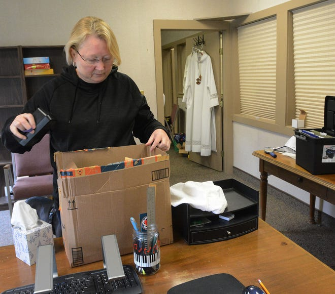 The Rev. Lisa Anderson packs up her office Tuesday after the last service at St. John Lutheran Church in Killingly.