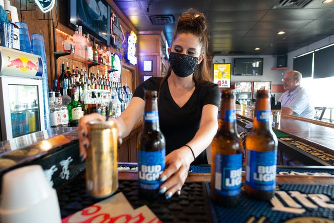 Megan Rice, server at Weller's Grill and Bar, 222 N.W. Independence Ave., preps drinks for customers along with one other server over the lunch hour Tuesday. Rice said they employ six servers but had 10-12 before the pandemic.