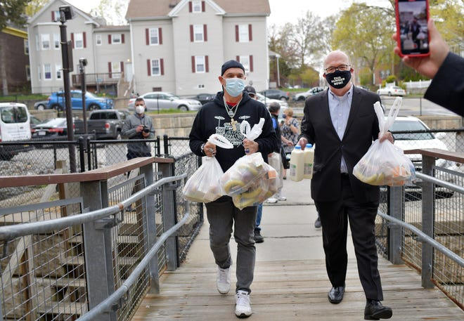 John Provost, left, a YMCA employee, and U.S. Rep. James McGovern deliver meals to 9 May St. Tuesday.
