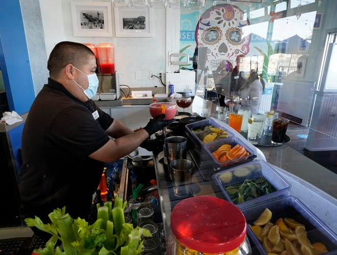 In this Wednesday, March 31, 2021 file photo, Barman Gustavo prepares drinks behind a plexiglass protective wall at Maria Sol on the Santa Monica Pier as the pier restaurant opens for indoors service in Santa Monica.