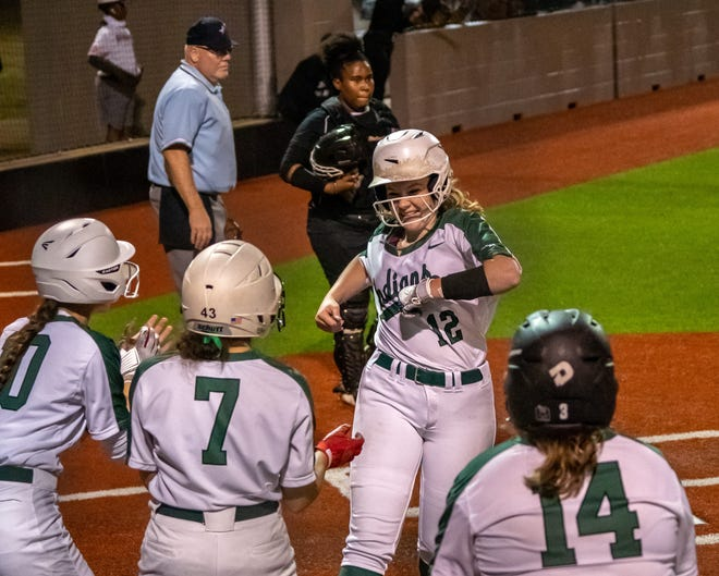 Waxahachie senior Lacee Hortman (12) is greeted at home plate while scoring during Friday's District 11-6A finale at the Midkiff Athletic Complex. The Lady Indians routed DeSoto, 18-0, in four innings and will open the Class 6A Region II playoffs against Bryan on Wednesday at Texas A&M University.