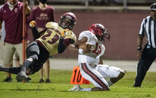 Lake Gibson's Jy'vonte McClendon (23) drives Kathleen quarterback Shadarian Harrison out of bounds during action in Lakeland, Fla.