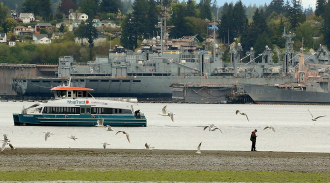 The Waterman passes a person walking out into the tide flats during low tide in Port Orchard on Tuesday, April 27, 2021.