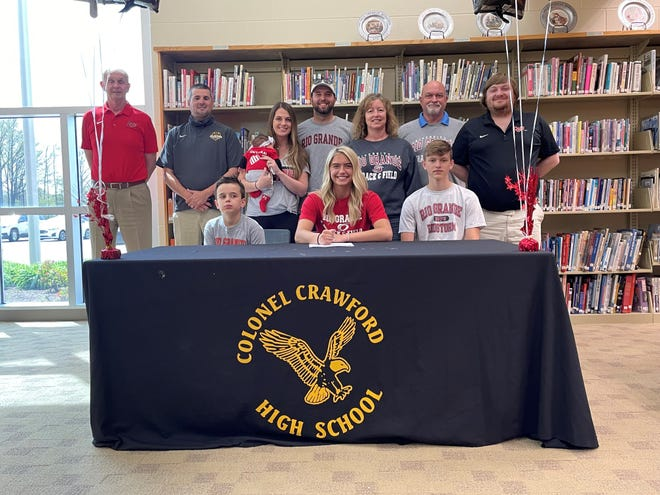 Cassidy Vogt, surrounded by family and coaches, signs her letter of intent to continue her track and field career at Rio Grande University.