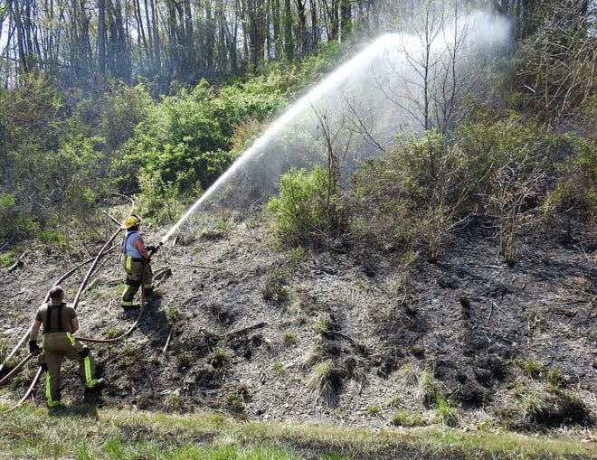 Firefighters put out hot spots along a steep bank in the area of Ohio 16 and County Road 6 Tuesday afternoon related to a brush fire.