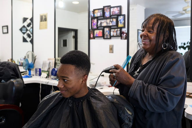 Marcia Lynch-Duncan, a veteran barber who owns and operates Lynch's House of Coiffure, laughs with Quan Boyde, not pictured, as she cuts his son 16-year-old Keion Boyde's hair in Evansville, Ind., Saturday afternoon, April 24, 2021. Lynch-Duncan's shop on Kentucky Avenue has been a fixture of locally-owned Evansville businesses since her mother opened it more than 40 years ago.