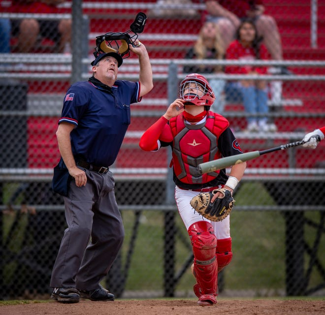 Umpire Greg Wright takes his mask off to better spot a fly ball in foul territory. Center Grove High School hosted Roncalli High School in IHSAA varsity baseball action Friday, April 23, 2021 in Greenwood. Center Grove won 10-0 in five innings.