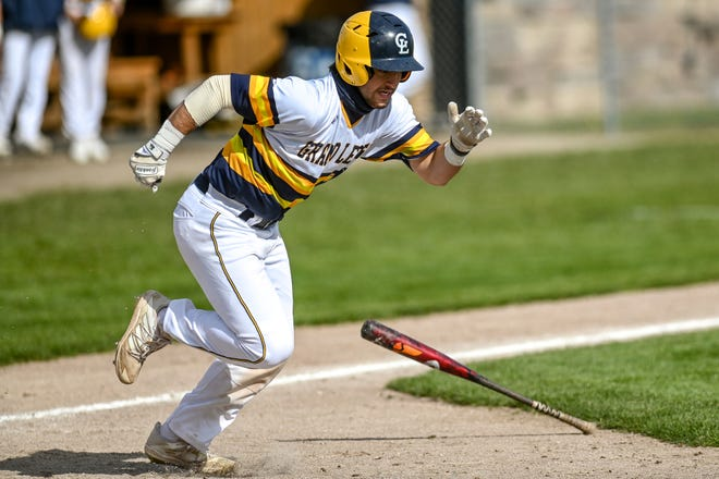 Grand Ledge's Logan Todd gets on base with a bunt against Okemos during the fourth inning on Monday, April 26, 2021, at Grand Ledge High School. Grand Ledge won 10-0.
